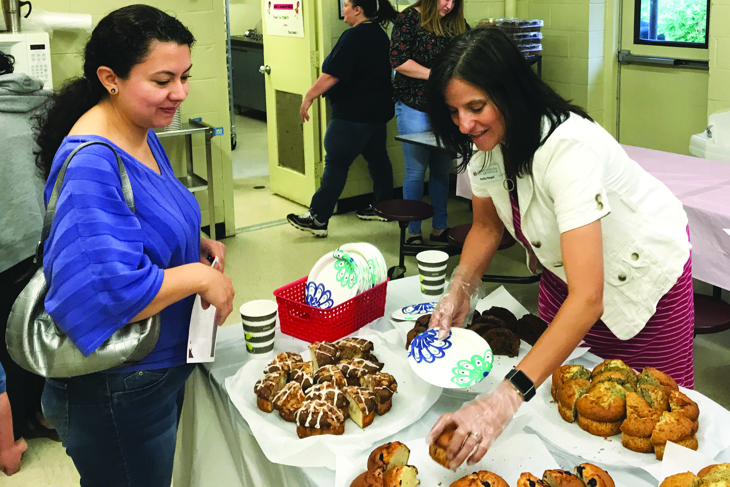 Credit Union of Georgia Business Development Officer Kelly Nagel serves up breakfast to a mom at Ralph Bunche Center.