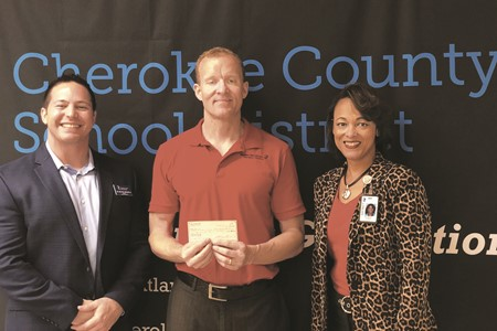 Garth Gherardini with Modern Woodmen of America, center, is thanked for his sponsorship of the Middle School Academic Bowl by CCSD Chief Academic Officer Dr. Nicole H. Holmes and Curriculum Director Dr. Michael Manzella.